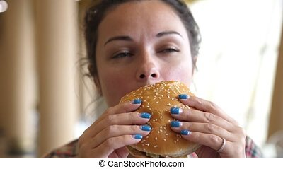 Girl eating a hamburger. close-up shot. Fast food eats. Burger in female hands.