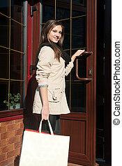 Young pretty woman entering shop