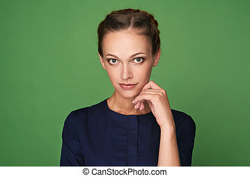 Young pretty woman face close up portrait. studio shot over green background