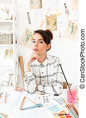 Young pretty woman fashion designer sitting at her work desk
