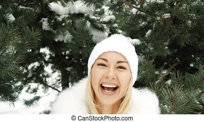 Young pretty woman flirt with camera in winter in forest.