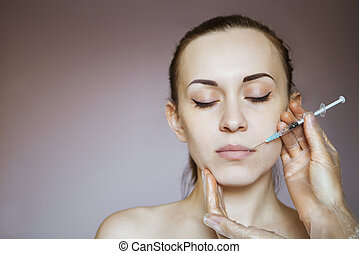 Young pretty woman getting cosmetic injection in the face...