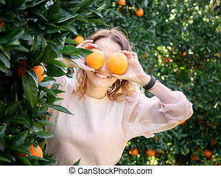 Young pretty woman holding oranges in front of eyes