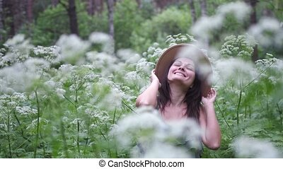 Young pretty woman in hat poses in magic forest on a background of white flowers.