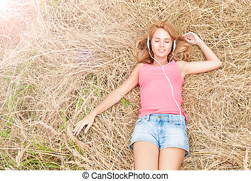 Young pretty woman in headphones on hay.