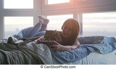 Young pretty woman in headphones relaxing with her lovely...