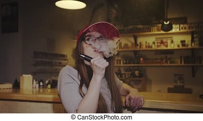 Young pretty woman in red cap smoke an electronic cigarette...