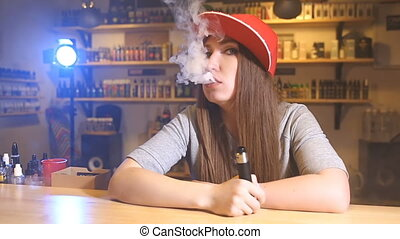 Young pretty woman in red cap smoke an electronic cigarette at the vape shop. Closeup.