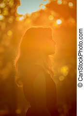 Young pretty woman in the autumn park profile view backlit by sunset headshot