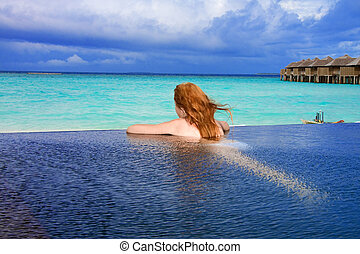 Young pretty woman in the pool and ocean in the background. Maldives