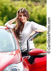 Young pretty woman in the red car