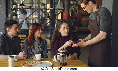 Young pretty woman is paying with smartphone for meal in...