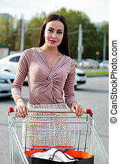 Young pretty woman is posing outdoors with shopping cart