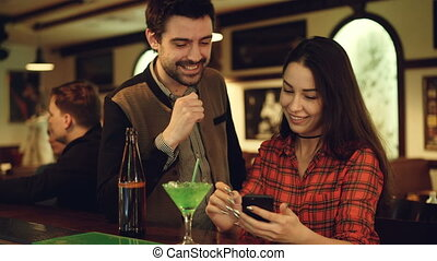 Young pretty woman is showing her boyfriend smartphone screen, they are watching, laughing and talking while spending night in bar. Modern entertainment concept.