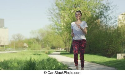 Young pretty woman jogging in summer