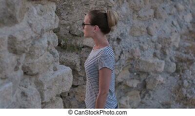 Young pretty woman looking at ancient ruins