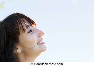 Young pretty woman looking at the sunny sky and smiling