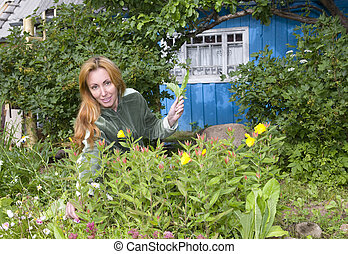 Young pretty woman looks after behind plants in the garden