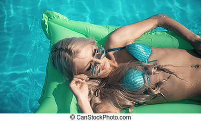 Young pretty woman lying on air mattress in the swimming pool