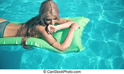 Young pretty woman lying on air mattress in the swimming...