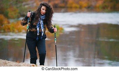 Young pretty woman on hiking. Scandinavian walk. Forest
