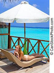 Young pretty woman  on platform at villa on water, Maldives