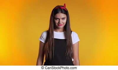 Young pretty woman on yellow background showing middle finger - gesture of fuck. Expression negative, aggression, provocation