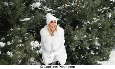 Young pretty woman play with snowballs in forest.