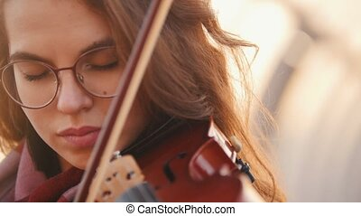 Young pretty woman playing violin solo in public, close view