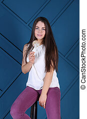 Young pretty woman poses on stool with lollipop in blue studio
