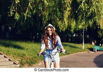 woman posing on the nature with bike i