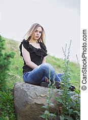 Young pretty woman posing sitting on a stone.