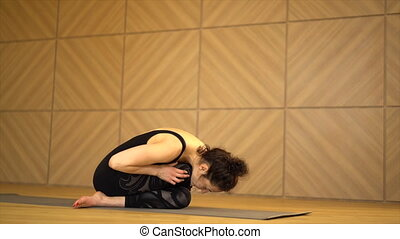 Young pretty woman practicing yoga at light minimalist...