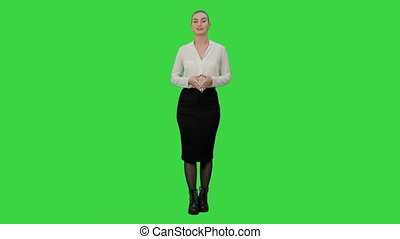 Young pretty woman presents something on a Green Screen, Chroma Key.