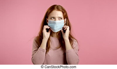 Young pretty woman puts on face medical mask during coronavirus pandemic. Portrait on pink background. Protection with respirator against COVID-19 outbreak. High quality 4k footage