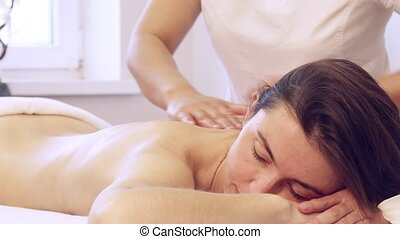 Young pretty woman enjoying Vietnamese body massage with aromatic oil at spa club