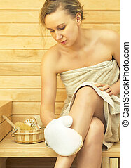 Young pretty woman relaxing in sauna.