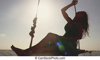 Young pretty woman relaxing swinging on a rope swing with a paradise tropical sea in background an the sun shining with lens flare effects. slow motion.