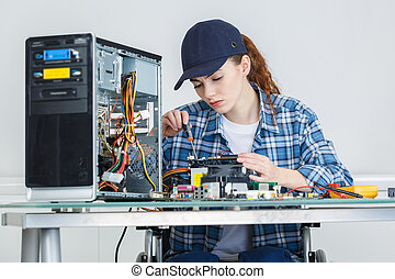 young pretty woman repairing computer