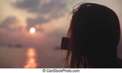 Young pretty woman sailing boat on sea during sunset takes...