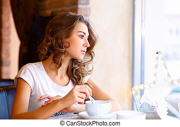 Portrait of young pretty woman sitting in restaurant