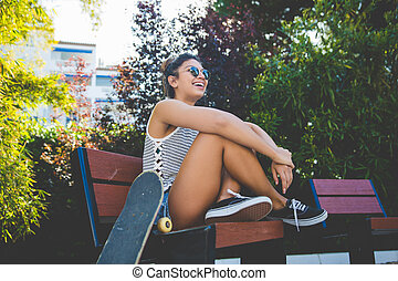 Young pretty woman sitting on beach with skateboard laughing