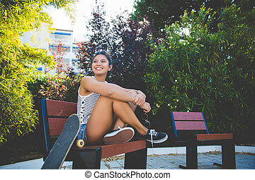 Young pretty woman sitting on beach with skateboard smiling