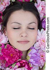 Young pretty woman sleeping among pink lilies