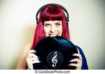 Young pretty woman smiling and biting vinyl record close up