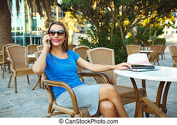Young pretty woman talking on the phone in a cafe
