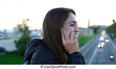 young pretty woman talking on the phone on a city bridge