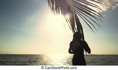 Young pretty woman touching palm leaf on the sun and the sea background. Girl poses on camera in slow motion with lens flare effects. 1920x1080