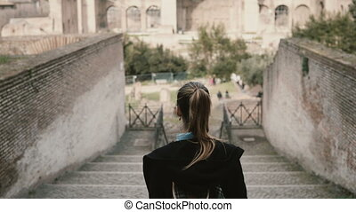 Young pretty woman- tourist moving down the stairs in the ancient centre of Rome, Italy to Roman Forum.