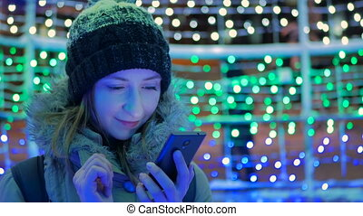 Young pretty woman using smartphone in the city at night